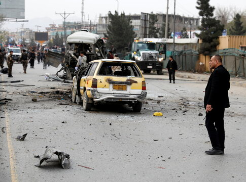 Afghan officials inspect a damaged minibus after a blast in Kabul