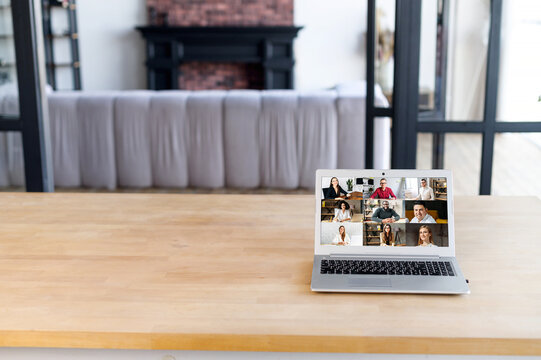 Many portraits faces of diverse young and aged people webcam view, laptop on the desk, empty space, while engaged in videoconference on-line meeting, group video call application easy usage concept