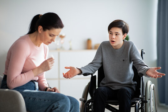 Conflict between parent and teenager. Sad mother crying, teen son in wheelchair making excuses or apologizing at home