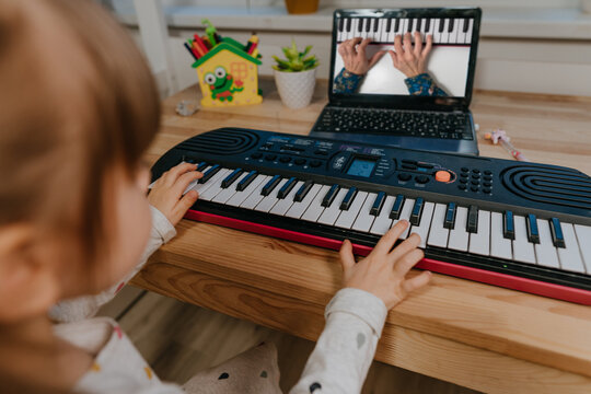 Little girl watching online lesson tutorial how to learn a synthesizer