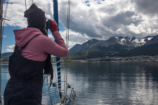 sailor looking through binoculars to locate beacons for the approach towards land