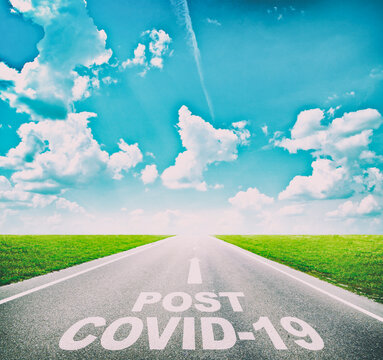 """The empty road between the meadow and the text on the asphalt """"Post covid19""""."""