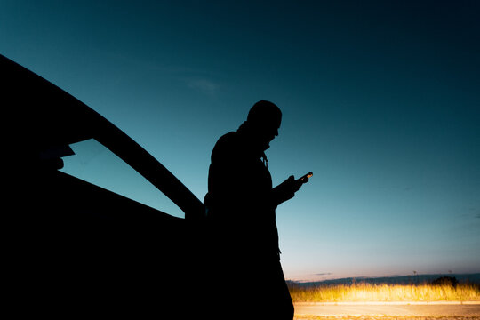 A man silhouetted against the evening sky, Looking at his phone