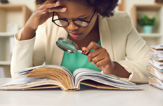 Closeup portrait of concentrated young african american woman auditor with magnifying glass scrutinizing financial documents at desk with paper folder pile in office. Investigation and audit checkup