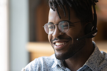 Fototapeta Close up of young smiling afro american guy wearing headset technical support worker dispatcher. Friendly black man call center operator in wireless headphones contact client glad to help. Copy space obraz