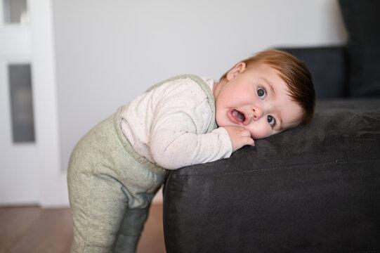 Amazed baby leaning on sofa
