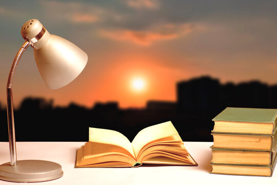 Books and a table lamp on the table against the backdrop of the setting sun.