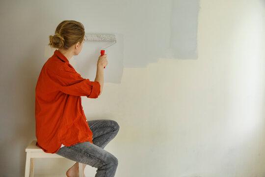 Focused woman painting walls in room