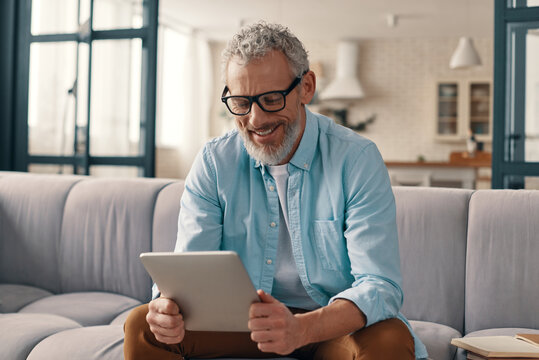 Cheerful senior man in casual clothing using digital tablet while sitting on the sofa at home