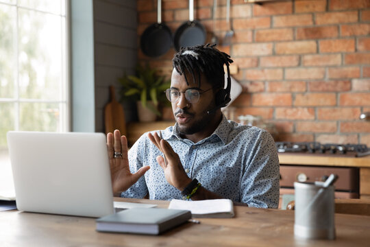 Young african male in headphones engaged in distant learning answer on teacher question at virtual class held by video conference. Millennial black man capable expert assist client online using laptop