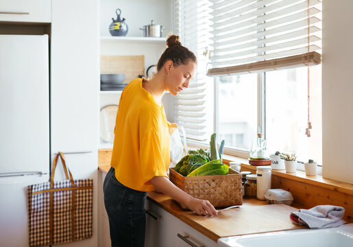 Woman with box of fresh vegetables reading paper card
