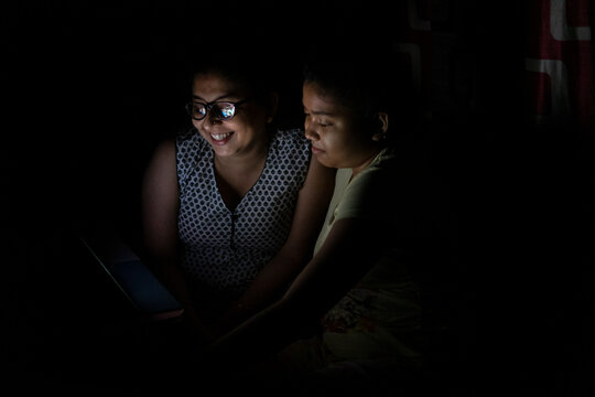 Mother and daughter watching movie inside room at night