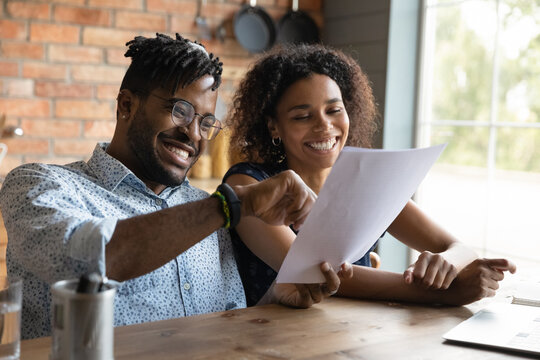 Excited young black husband wife read paper loan mortgage contract life insurance policy satisfied with good conditions offered. Smiling african couple receive tax refund letter glad to get money back