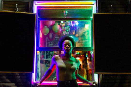 Attractive black woman leaning on windowsill of bar at night looking at camera.