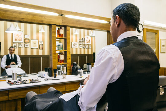 Barber working with customer in salon