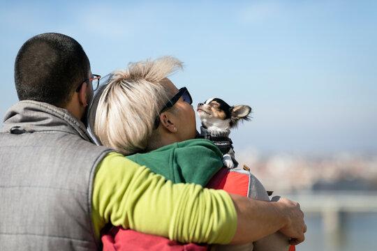 Hugged couple holding their dog
