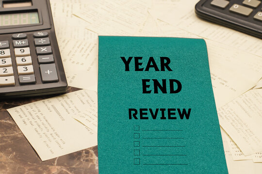 YEAR END REVIEW text on a blue piece of paper on a writing desk