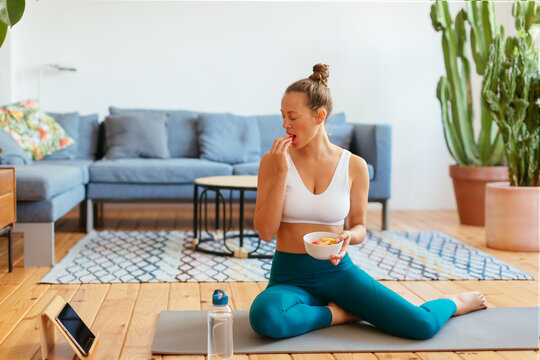 Female athlete eating healthy food and watching video