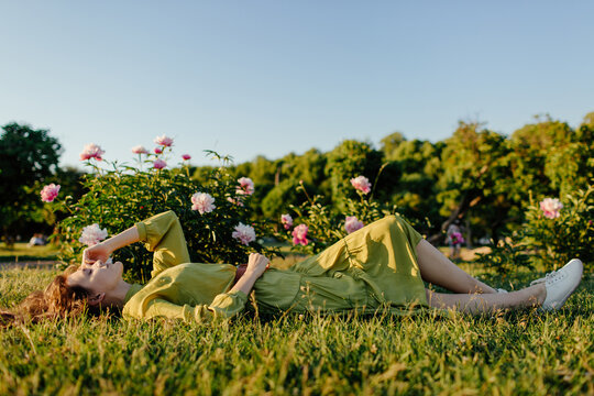 Young woman relaxing on green lawn in park