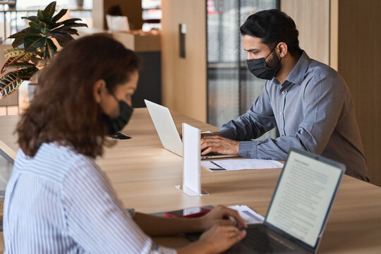Indian business man student wearing face mask working on laptop safe distancing. Diverse people in facemasks using computers sitting at table with social distance sign in office coworking or cafeteria