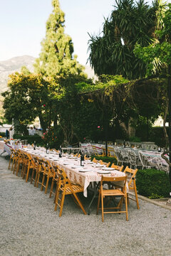 Spanish outdoor wedding venue with very long table with wooden folding chairs