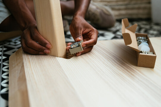 Anonymous person assembling wooden furniture