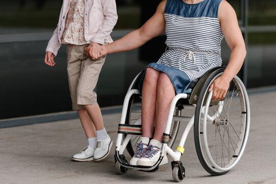 Crop woman on wheelchair riding near daughter