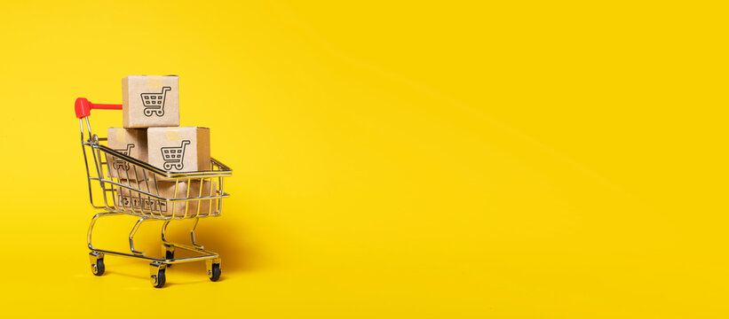 paper boxes parcel in a trolley isolated on yellow background. shopping online and service  home delivery.