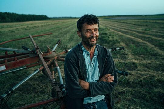 A Farmer is smiling after harrowing a field