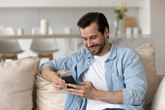 Smiling millennial Caucasian man sit on couch at home have fun using modern cellphone gadget. Happy young male relax on sofa look at smartphone screen texting or messaging online. Technology concept.