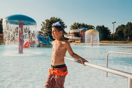 Boy standing water at pool.