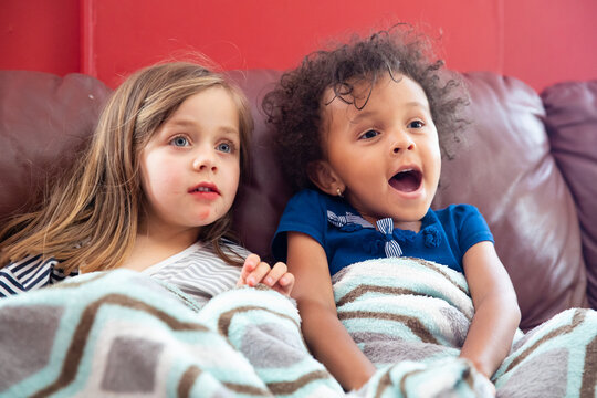 Two children of different races sit together and watch a television programme.