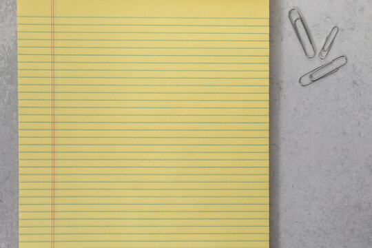 Close up of yellow legal pad of lined paper with office paper clip lay flat background
