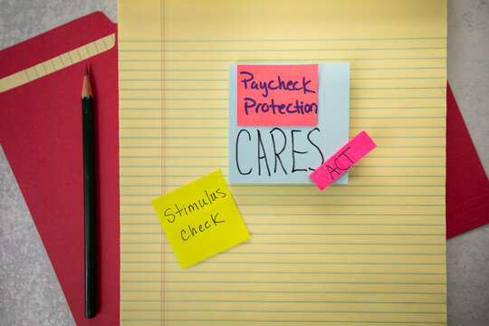 Paycheck protection CARES Act stimulus handwritten on posted notes on top yellow legal lined pad. Financial industry.