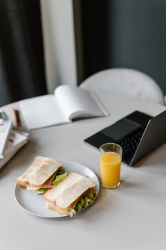Laptop and notebook near sandwiches and juice
