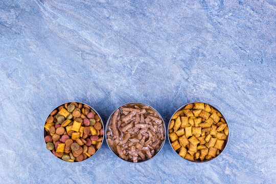 Dry and wet pet food. Copy space. Bowls with cat food on gray background.