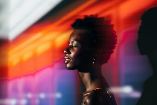 Black african woman posing in the studio with colorful lights