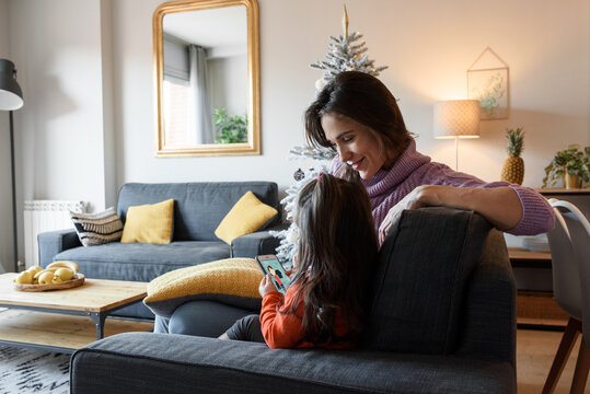 Happy mother and daughter using smartphone on sofa