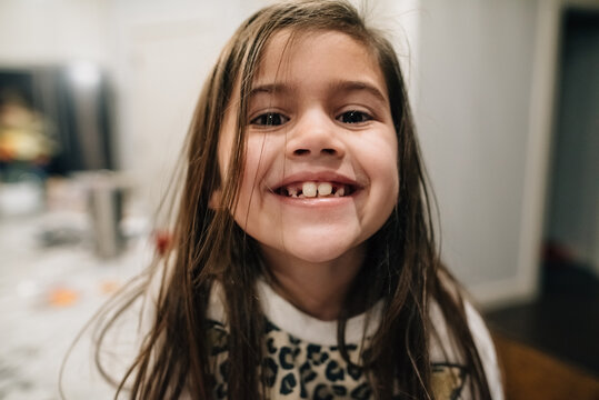 Young girl showing off new lost tooth.
