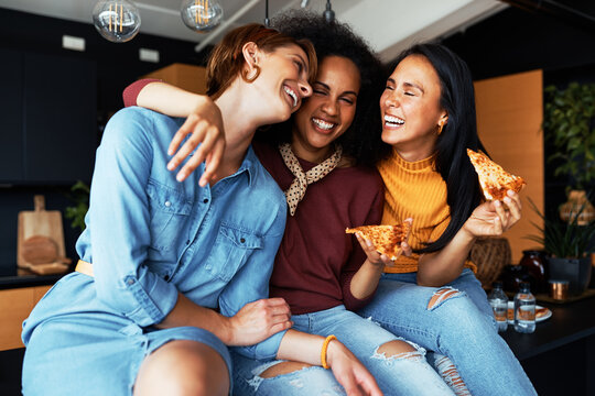 Diverse friends laughing and eating pizza