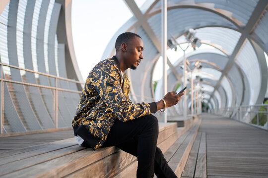 Cool Black Man Sitting With Phone Outdoors.