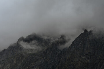 a group of mountain peaks covered with clouds
