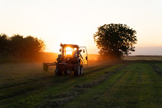 Tractor working on the field at sunset