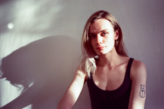 Portrait of an androgynous model in black dress with it's shadow