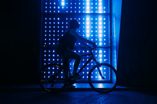 Woman on bicycle at night against blue neon background