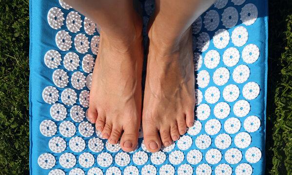 Crop person standing on acupressure mat