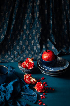 Pomegranate whole and cut in a contrasting still life image