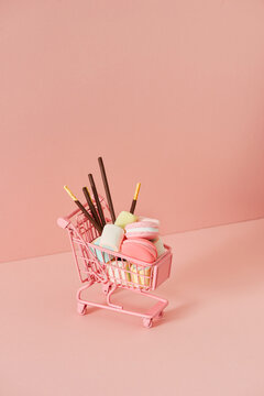 shopping cart full of candies on a pink background