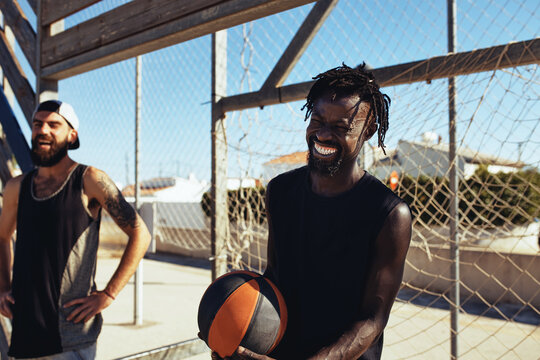 Laughing friends waiting to play basketball