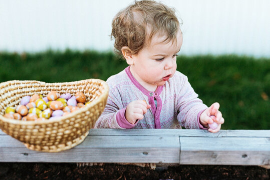 little girl in pajamas searching for eggs on easter day